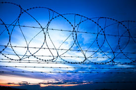 stock photo of barbed wire fence  - sunset behind the barbed wire  - JPG