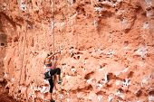 pic of ascending  - Determined female climber ascending a red rock in Utah - JPG