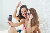 stock photo of laugh out loud  - Female friends laughing having fun taking selfie together wearing bikini bra swimsuit summer sunny day street urban casual style - JPG