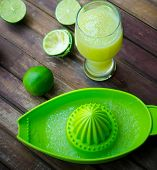 stock photo of juicer  - green limes with green manual juicer on the table - JPG