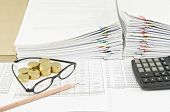 picture of spectacles  - Brown pencil with spectacles and gold coins have pile of paperwork as background - JPG