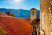 image of red roof tile  - Top view with tiled red roofs and mountains in Kotor old city in Montenegro - JPG