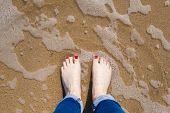 picture of painted toenails  - Feet view of bare feet with painted toenails standing in the water on a beach  - JPG