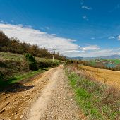 image of dirt road  - The Dirt Road Leading to the Mountain Lake Surrounded by Forests and Plowed Fields in Italy - JPG