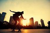 stock photo of skateboarding  - young skateboarder skateboarding ollie trick at sunrise city - JPG