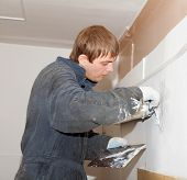 picture of putty  - Plasterer at indoor renovation decoration with putty knife in stained overalls - JPG