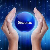 stock photo of give thanks  - Hand showing blue crystal ball with gracias word  - JPG