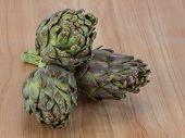 foto of artichoke hearts  - Fresh Raw artichokes on the wooden background - JPG