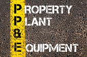 image of ppe  - Business Acronym PP&E - Property plant and equipment. Yellow paint line on the road against asphalt background. Conceptual image - JPG