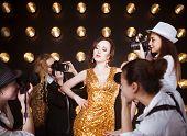 foto of superstars  - Superstar woman wearing golden shining dress posing to paparazzi - JPG