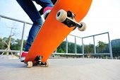 stock photo of skateboarding  - young skateboarder legs skateboarding at skatepark ramp - JPG