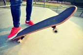 pic of skateboarding  - young skateboarder legs skateboarding at skatepark ramp