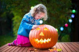 stock photo of jack o lanterns  - Little girl carving pumpkin at Halloween - JPG