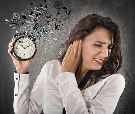 image of annoying  - Woman annoyed by the sound of alarm - JPG