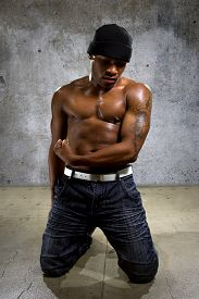 image of abdominal  - Muscular black male in hip hop style clothing showing abdominal muscles - JPG
