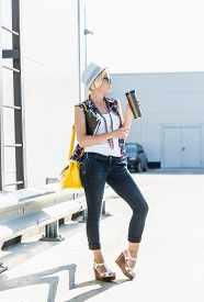 stock photo of thermos  - Stylish hipster girl drinking coffee from thermos at parking lot - JPG