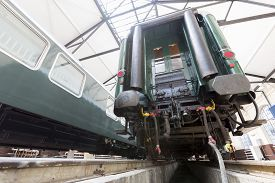 stock photo of passenger train  - Old authentic green passenger trains in a depot for renovation before being used for tourist trips across Europe - JPG