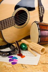 stock photo of bongo  - Vertical photo of several music instruments as bongo acoustic guitar harmonica rattles and few picks on paper sheets with notes - JPG