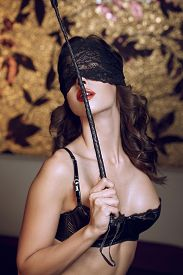 stock photo of latex woman  - Sexy woman in lace eye cover holding whip bdsm - JPG