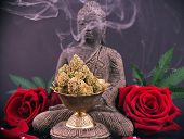 Zen smoky background with buddha statue, red roses and cannabis buds - medical marijuana and meditat poster