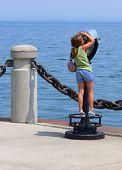 foto of burlington  - An little girl on an telescope looking over the lake Ontario on the lake promenade in Burlington.   - JPG