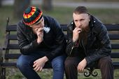 Two men smoking weed while sitting on bench outdoors poster