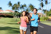 Happy runners couple having fun running training together in summer outdoors. Asian woman with perso poster