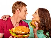 Couple eating fast food. Man and woman eat hamburger with ham. Friends holding burders junk on isola poster