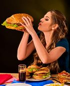 Woman eating french fries and hamburger with pizza. Student consume fast food on table. Girl trying  poster