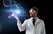 science, genetics and people concept - male doctor or scientist in white coat and safety glasses wit poster