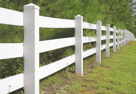 stock photo of white vinyl fence  - A long decorative white split rail fence - JPG
