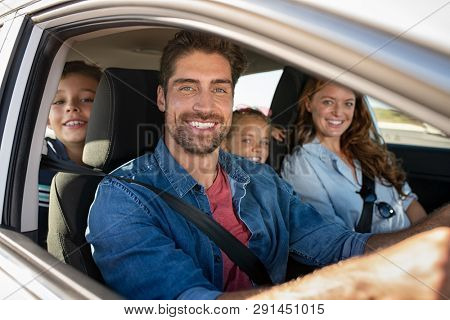 poster of Smiling young family with two children sitting in car and driving. Family relaxing during road trip