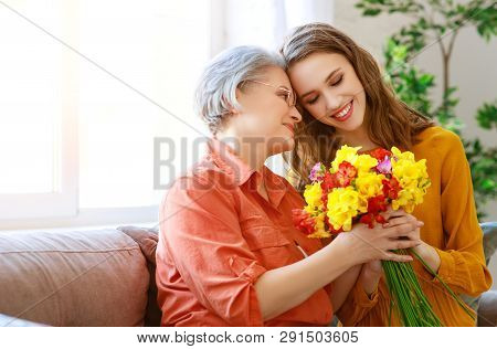 poster of Happy Mother's Day! Adult Daughter Gives Flowers And Congratulates An Elderly Mother On Holiday