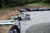 pic of sand gravel  - Installing a sand and gravel filter for a domestic septic tank system showing the plastic liner for the trench with sand in position and a pile of gravel waiting to be spread after the upper pipes have been connected  - JPG