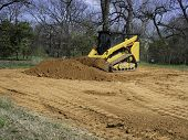 Skidsteer Loader Getting A Bucket Load Of Dirt From A Pile Of Dirt poster