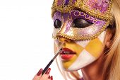 stock photo of venice carnival  - sexy woman in half mask from Venice brush her lips - JPG
