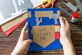 The Child Holds Greeting Card With Happy Fathers Day. Childrens Art Project Craft For Kids. Craft F poster