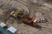 An Industrial Excavator Filling Up A Dump Truck. Construction Excavator Industrial Site. Backhoe Loa poster