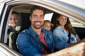 Smiling young family with two children sitting in car and driving. Family relaxing during road trip  poster