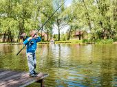 Boy Fishing From A Wooden Dock On A Lake Or Pond Pier In A Sunny Summer Day. Back View Of A Little 5 poster