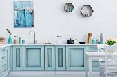 Interior Of Modern Turquoise Kitchen With Painting On White Brick Wall poster