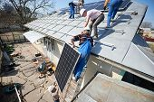 Male Team Workers Installing Stand-alone Solar Photovoltaic Panel System. Electricians Lifting Blue  poster