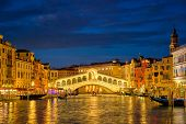 Famous Venetian tourist landmark Rialto bridge (Ponte di Rialto) over Grand Canal illuminated at nig poster