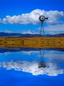 Windmill on hillside in countryside rural America with sky and clouds reflection in water like a lke poster