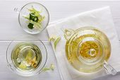 Linden Tea In A Transparent Tea Pot.  Glass Cup And Tea Pot With Herbal Lime Tree Tea On White Backg poster