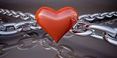 Shiny red heart and a chain on a dark gray background