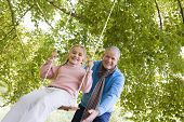 Grandparent Pushing Child On Swing