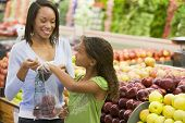 pic of grocery store  - Woman and daughter shopping for apples at a grocery store - JPG