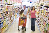 stock photo of grocery store  - Mother and father with young daughter shopping for a car - JPG