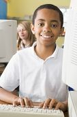 image of tweeny  - Student at computer terminal typing with student in background  - JPG